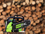 Electric Cordless battery powered chainsaw Greenworks in front of a stacked pile of firewood in the background