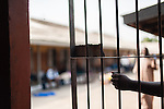 The hand of a patient entrusted with admitting visitors (under the supervision of staff) is seen at a gate to a ward at the Accra Psychiatric Hospital.