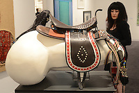 "A woman looks at a mixed media sculpture entitled ""The Gallop of History,"" (2010) by artist Hossein Edalatkhah during the preview of Art Platform - Los Angeles at The Barker Hangar on Thursday, September 27, 2012."