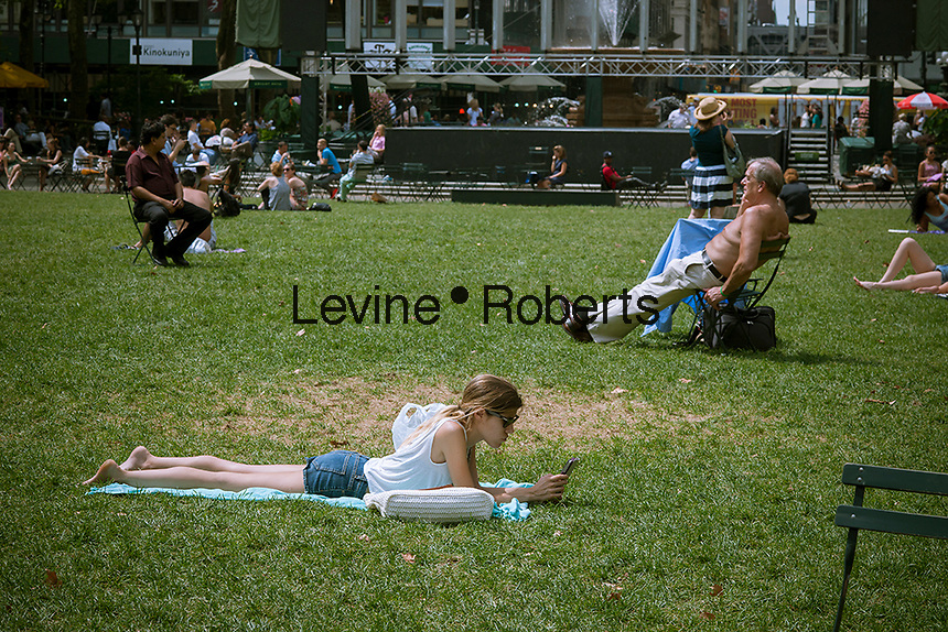 A visitor to Bryant Park in New York uses her tablet computer on Wednesday, July 31, 2013.  (© Richard B. Levine)