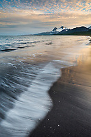Landscape of waves washing up along the sandy beach of Katmai National Park, Aleutian mountain range, Alaska Peninsula, southwest Alaska.