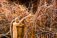 A statue of an angel with horn welcomes the holiday season in Rice Park. The lighted trees and decorations are a holiday tradition in downtown St. Paul, Minnesota.