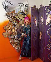 Portrait of Zandra Rhodes posing between a mirrored, mosaic artwork and a hand-painted purple screen