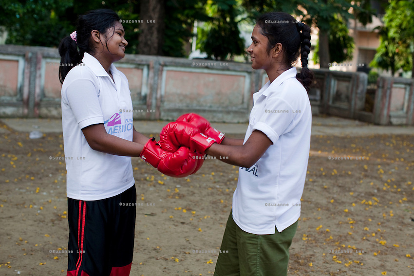 Teenaged girls touch gloves before begining their sparring session as Razia Shabnam (unseen) conducts a boxing training session with a group of girls from an NGO in a park in Basduni, Tolly Gunge, Calcutta, West Bengal, India. Razia Shabnam, 28, was one of the first women boxers in Kolkata. She was also the first woman in her community to go to college. She is now a coach and one of only three international female boxing referees in India.  Photo by Suzanne Lee for Panos London