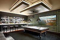 A luxurious games room with a bar and a pool table in the centre set on a grey rug.