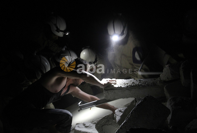 Syrian rescue workers search under the debris of a building following a reported bomb barrel attack by Syrian government forces, in Karm el-Beik rebel held district in the northern Syrian city of Aleppo, June 7, 2015. At least 10 civilians were killed and many others were injured on following Syrian regime barrel bomb attacks on Aleppo. Photo by Ameer al-Halbi