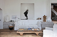 The living room is simply furnished with a sofa draped in a white cotton loose cover, flanked by a pair of wooden coffers and facing a rustic coffee table