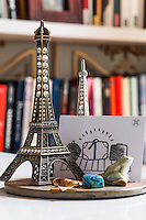 A model of the Eiffel Tower stands against the bookcase in the living room