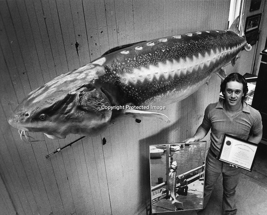 Joey Pallotta standing along side his 468 lb. sturgeon <br />fish was estimated to be 100 years old and measured 9 feet long. He caught the fish in the bay near Crockett, California. (1983 photo by Ron Riesterer)