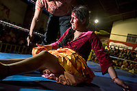 17 year old wrestler Alicia Flores (fighting name), Patricia Kaly (real name) on the ground during a fight at the Multifuncional building in El Alto. Patricia is a Cholita, a wrestler of native Aymara descent. When Cholitas fight they wear traditional costume. The blood on Patricia's face is believed to be fake, but the wrestlers insist that it is real. .