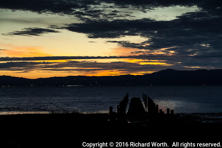 Sunset glows while long-abandoned pilings and pier  stretch into San Francisco Bay.