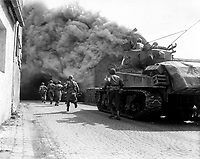 Soldiers of the 55th Armored Infantry Battalion and tank of the 22nd Tank Battalion, move through smoke filled street.  Wernberg, Germany.  April 22, 1945.  Pvt. Joseph Scrippens.  (Army)<br /> NARA FILE #:  111-SC-205298<br /> WAR &amp; CONFLICT BOOK #:  1094