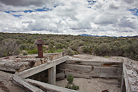 A rusty, bullet-punctuated stovepipe atop timbers, the remains of a dugout structure at the ghost town Cobre, Nevada.