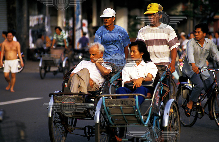 Western businessman being driven through the streets of downtown Saigon/Ho Chi Minh city in a cyclo.  Credit: Chris Stowers.