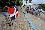 Children observe as the national flag is displayed after being lowered at the end of the day at a school in Batey Bombita, a community in the southwest of the Dominican Republic whose population is composed of Haitian immigrants and their descendents.