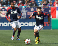 New England Revolution midfielder Kelyn Rowe (11) on the attack.  In a Major League Soccer (MLS) match, the New England Revolution (blue/white) tied Vancouver Whitecaps FC (white), 0-0, at Gillette Stadium on March 22, 2014.