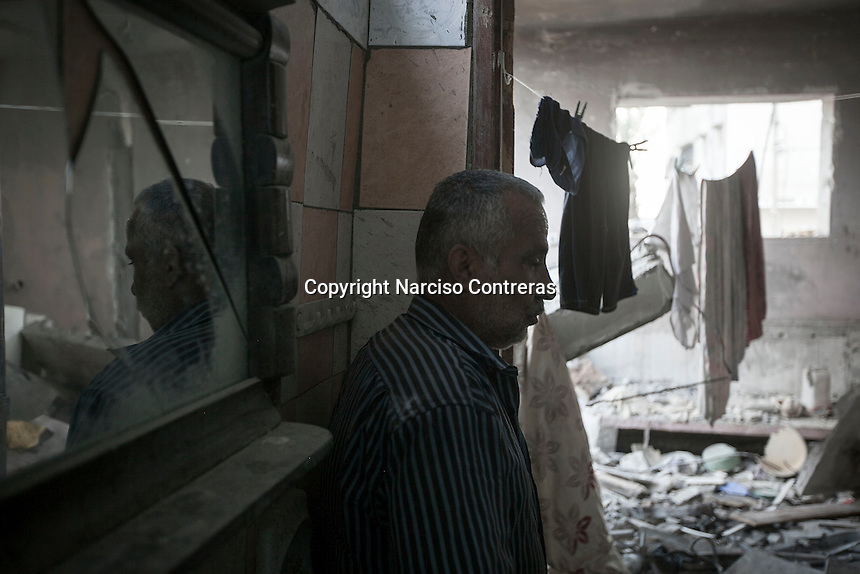 """In this Friday, Aug. 15, 2014 photo, a Palestinian man stands at the living room of his house -where he and his family still living- that was partially destroyed by an israeli airstrike during the """"Protective Edge"""" military operation in Shuyaja neighborhood in Gaza City. After a five days truce was declared on 13th August between Hamas and Israel, civilian population went back to what remains from their houses and goods in Gaza Strip. (Photo/Narciso Contreras)"""