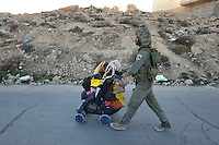 An Israeli soldier pushes a pram full of Jewish settlers' belongings after the army evicted the settlers from a disputed building in Hebron. The Israeli high court had rejected the settlers' claim that they legally bought the house from its Palestinian owner. As the house became a symbol of defiance, the few families living there were joined by a mob of some 1,500 radical right-wing youths, who went on a rampage and attacked Palestinians in the mixed West Bank city.