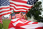 Larry Westfall of Pearland sets out more American Flags in the lot, on FM 518 in League City,  where he and his wife, Lesli,  are selling them. They have sold flags on the lot, as a family tradition, for the last 15 years during the week of the 4th of July.   Tuesday, July 3, 2007, in Houston. ( Steve Campbell / Chronicle)