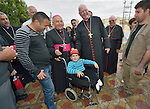 Cardinal Timothy Dolan, the archbishop of New York and chair of the Catholic Near East Welfare Association, places his zucchetto on Henry Samir, a 6-year old child with disabilities, outside the Mar Narsai Clinic in Dahuk, Iraq, on April 10, 2016. The clinic was built and equipped by CNEWA to meet the needs of Christians and others displaced to Dahuk because of attacks by ISIS.<br /> <br /> Standing beside Cardinal Dolan is Bishop Shlemon Warduni, the auxiliary bishop of the Patriarchate of Babylon.<br /> <br /> Cardinal Dolan came to Iraqi Kurdistan with Bishop William Murphy of Rockville Centre and other church leaders to visit with Christians and others affected by ISIS. <br /> <br /> CNEWA is a papal agency providing humanitarian and pastoral support to the church and people in the region.