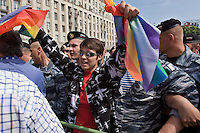 Moscow, Russia, 27/05/2007..A gay activist waves a banner in front of riot police just before being arrested at Moscow's second attempted Gay Pride parade. The parade had already been banned by Moscow Mayor Yuri Luzhkov on the grounds that it would provoke violence, but gay activists attempted to demonstrate in defiance of the ban, and many were beaten by counter demonstrators and arrested by police.