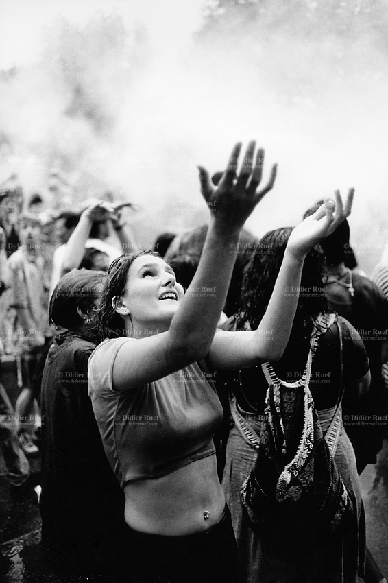 Switzerland. Zürich. A young woman dances with both her hands open to the sky during the Street Parade which is a yearly techno event in Zurich. © 1995 Didier Ruef