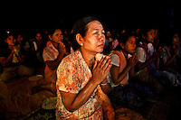 Supporters from Kyaw Min pray as U Wirathu (unseen), the spiritual leader of the Buddhist nationalist 969 Movement, gives a sermon at the Shwe Areleain Monastery in Kyaw Min Village, Myiamu Township. U Wirathu is an abbot in the New Maesoeyin Monastery where he leads about 60 monks and has influence over more than 2,500 residing there. He travels the country giving sermons to religious and laypeople encouraging Buddhists to shun Muslim business and communities. /Felix Features