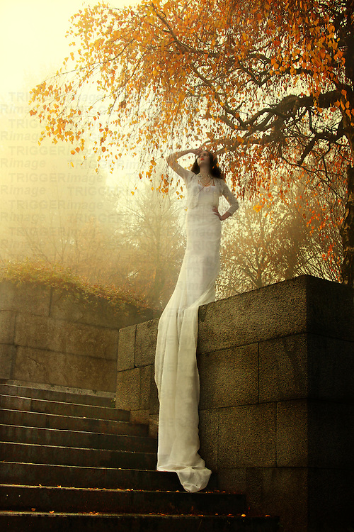 A woman in a long white gown standing in the morning light under a tree on top of a staircase.