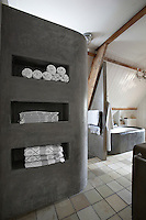 In the bathroom the walls and bath are made of polished concrete with storage alcoves for bath linen