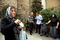 "Italy. Lazio region. Tivoli. Several people, all romanian citizens, talk together after the orthodox sunday mass. An old woman eats Koliva (Romanian, colivă ) in a white plastic glass. While recipes may vary widely, the primary ingredient of Koliva is wheat kernels, which have been boiled until they are soft, and then sweetened with honey, sugar, and some fruit. It may also contain sesame seeds, almonds, ground walnuts, cinnamon, sugar, pomegranate seeds, raisins, anise and parsley. Romanians also decorate the koliva with crosses of cocoa, chocolate or candy. The orthodox religious service took place in a catholic church "" Chiesa di San Pietro alla Carita"". Romanian immigration. Tivoli is a town and comune in the province of Rome.  02.10.2011 © 2011 Didier Ruef"