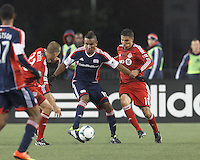 New England Revolution midfielder Juan Agudelo (10) dribbles as Toronto FC defender Ryan Richter (33) and Toronto FC forward Luis Silva (11) defend. In a Major League Soccer (MLS) match, the New England Revolution (blue) defeated Toronto FC (red), 2-0, at Gillette Stadium on May 25, 2013.