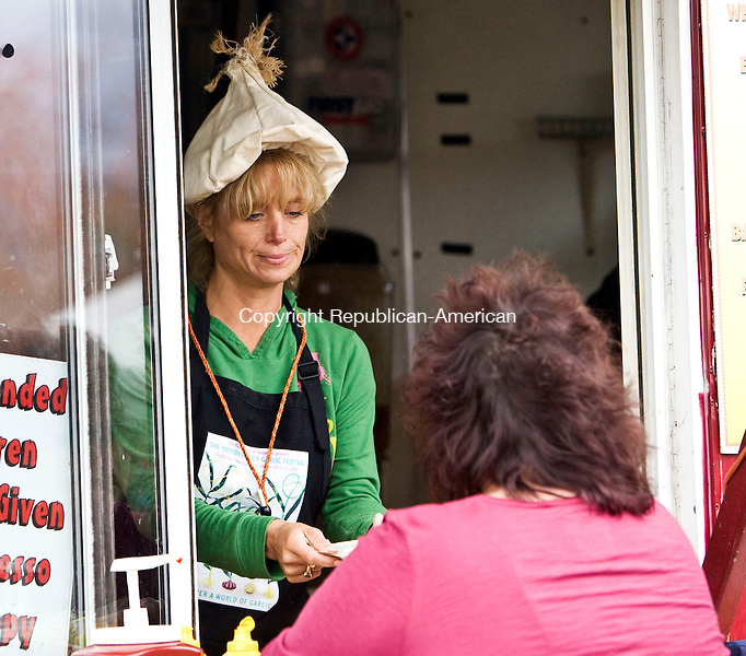 BETHLEHEM, CT - 10 OCTOBER 2009 -101009JT06-<br /> Wearing a garlic hat, Tracy Krawitt sells Michelle Brown of Beacon Falls an order of fried garlic cloves at the Spacey Tracy food booth during Saturday's fifth annual Bethlehem Garlic and Harvest Festival at Bethlehem Fairgrounds. <br /> Josalee Thrift Republican-American