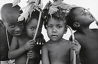 Young children holding banana leaves to shade themselves in Brazil.