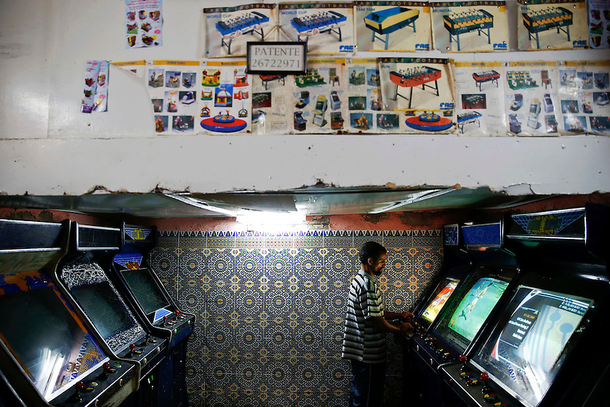 """A man plays video games in an entertainment salloon in Rabat's Medina September 21, 2014. Behind walls of Medina and Kasbah of the Oudayas, ancient neighbourhoods of Morocco's capital, labyrinths of small alleys, colourful buildings and street markets offer a glimpse into city's rich history. Rabat was recently listed by UNESCO as a World Heritage Site and suggested as a """"must see"""" destination by major media outlets and tourist agencies.  REUTERS/Damir Sagolj (MOROCCO)"""