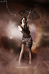Female standing high in a storm holding a black lace umbrella with lightening
