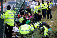 Arrested protesters watch as police tend to an injured colleague as climate activists take direct action against the coal fired power station at Ratcliffe on Soar, south of Nottingham. The power station, owned by E.ON, is the third largest emitter of greenhouse gases in the UK.