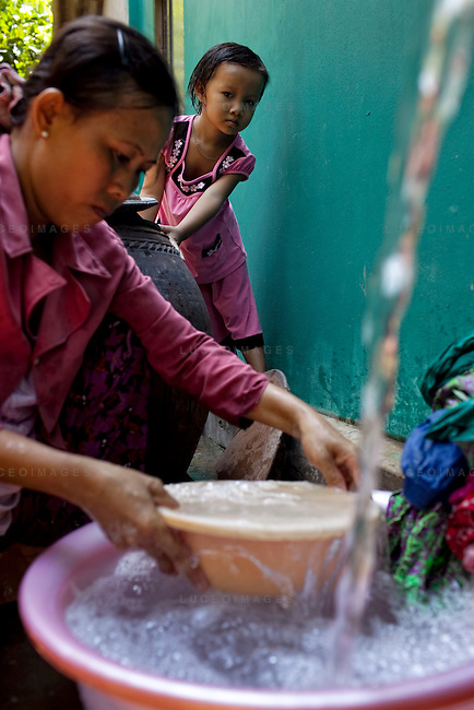 Hien, 4, watches as her aunt Doan Thi Ut, 43, washes her laundry in clean water provided by the Tien Phat enterprise in the Luong Hoa Lac commune.