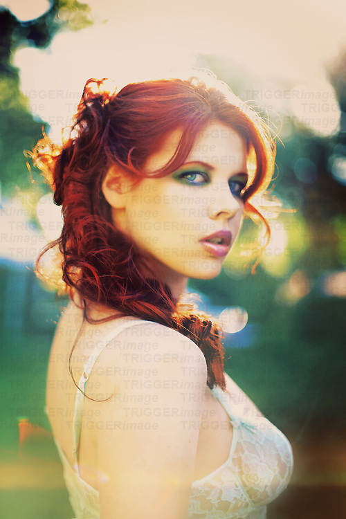 Close-up of a young woman with red hair turning away but staring back with a sad expression outdoors