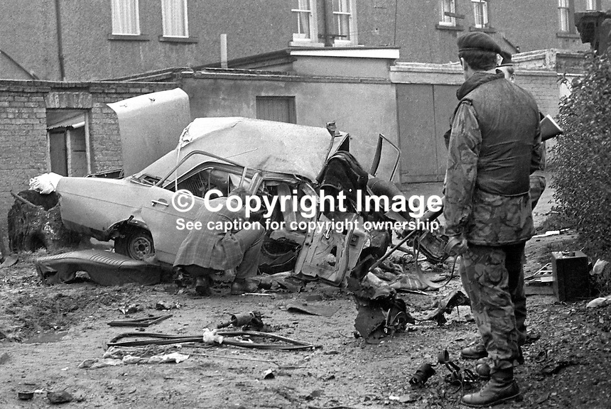 Remains of the booby-trapped car at the rear of his home in which Edward Clayton, 27 years, breadserver, Armagh, N Ireland, died on 6th March 1975. The explosion was believed to have been carried out by the Provisional IRA but almost certainly they got the wrong man as Clayton had no security force or para-military connections. The victim's brother would almost certainly have died in the explosion had he not gone back at the last minute to get a raincoat. Soldiers stand guard as forensics officer investigates. 197503060205..Copyright Image from Victor Patterson, 54 Dorchester Park, Belfast, UK, BT9 6RJ..Tel: +44 28 9066 1296.Mob: +44 7802 353836.Voicemail +44 20 8816 7153.Skype: victorpattersonbelfast.Email: victorpatterson@me.com.Email: victorpatterson@ireland.com (back-up)..IMPORTANT: If you wish to use this image or any other of my images please go to www.victorpatterson.com and click on the Terms & Conditions. Then contact me by email or phone with the reference number(s) of the image(s) concerned.
