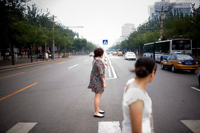 Pedestrians wait for traffic to clear to cross the street to an Olympic venue in Beijing, China on Wednesday, August 6, 2008. The city of Beijing is gearing up for the opening ceremonies of the Olympic Games.  Kevin German