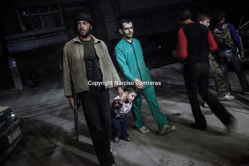 Omar, four years-old, walks hand by hand with his father, Dr. Osman and a rebel fighter at the street outside of the Dar Al-Shifa hospital, where they live and spend most of the 24 hours of the day. Dr Osman went to live with his family at the hospital knowing that it was a target for the Syrian air force. Fatimah, his wife, decided to go with him following her husband's desire to stay permanently working and living at the hospital due the lack of doctors to help. The hospital was targeted more than twenty times by aircraft and mortar shelling; despite the bombing had dameged the hospital structure, the medical staff was still operating and providing medical care to the local residents.