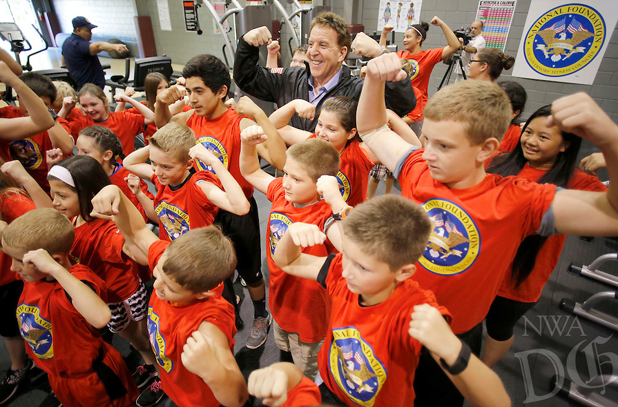 NWA Democrat-Gazette/DAVID GOTTSCHALK  Jake Steinfeld (back center), chairman of the National Foundation for Governors' Fitness Councils and personal fitness television personality, poses Wednesday, October 7, 2015 with Lincoln Middle School students as they display their muscles within the new Live Positively Fitness center at the school.The school is one of three in the state named a National Champion School by the National Foundation for Governors' Fitness Councils and received a $100,000 fitness center that includes 46 pieces of equipment from Tuff Stuff Fitness International. Martin Luther King Magnet Elementary in Little Rock and S.C. Tucker Elementary School in Danville also received a new fitness center.