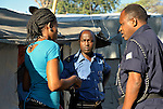"A woman in the Petionville Camp at the edge of Port au Prince, Haiti, is interviewed by police officials after lodging a domestic violence complaint against her husband. Some 50,000 residents are packed onto what was once a golf course, and the close quarters and frustration at lack of employment and other opportunities contributes to tensions, according to Pascal Rwatangabo (right), a Rwandan officer with the United Nations MINUSTAH police force. ""With nothing to do but sit in their tent all day under the sun, it's not surprising to see problems,"" Rwatangabo said. ""And when the men start drinking, it's even worse. Yet when we start to arrest a man for a violent crime, the woman will often plead with us to let him go, because she realizes her precarious economic situation will deteriorate if the man is not there, even though his violent behavior may continue."" Also present was MINUSTAH official Aphrodis Nkandineza (center). The Petionville Camp is the largest camp of hundreds of locales hosting more than a million people left homeless by the January 12, 2010 quake."