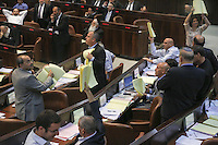 Knesset members of the Balad and Hadash parties point at empty pages as they hold up copies of the state budget proposal during a plenum session voting on the state budget, in the Knesset, Israel's Parliament, in Jerusalem, late night July 29, 2013. The Knesset approved the State Budget at second and third readings in the early hours of Tuesday morning in a 58-43 vote, following a 15-hour parliamentary session. Photo by Oren Nahshon