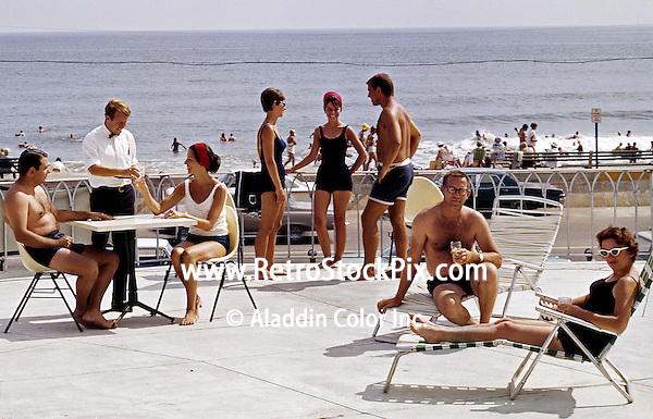 Couples on the sundeck being served drinks from a waiter.