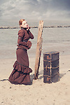 Young woman in a victorian dress standing next to an old suitcase alone outdoors beside the sea