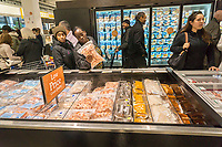 Shoppers choose frozen seafood in the new Whole Foods Market in Newark, NJ on opening day Wednesday, March 1, 2017. The store is the chain's 17th store to open in New Jersey. The 29,000 square foot store located in the redeveloped former Hahne & Co. department store building is seen as a harbinger of the revitalization of Newark which never fully recovered from the riots in the 1960's.  (© Richard B. Levine)