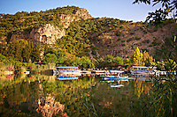 Boats on Dalyan Çay River with Lycian Rock Tombs in the cliffs . Mediterranean coast Turkey