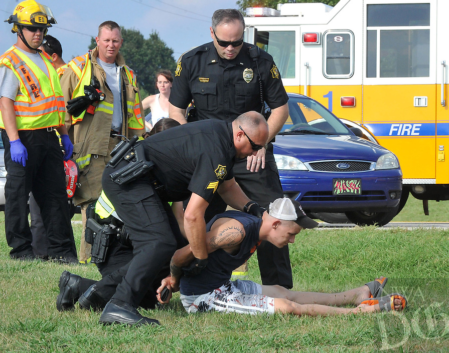 NWA Media/Michael Woods --09/09/2014-- Springdale police officers place a man under arrest after a two car accident involving a van and a school bus on Old Wire Road in Springdale Tuesday afternoon.