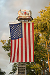 Garden City, New York, U.S. - June 6, 2014 - A large American Flag was suspended from a cherry picker high over the intersection of Franklin Avenue and 7th Street, during the 17th Annual Garden City Belmont Stakes Festival, celebrating the 146th running of Belmont Stakes at nearby Elmont the next day. There was street festival family fun with live bands, food, pony rides and more, and a main sponsor of this Long Island night event was The New York Racing Association Inc.